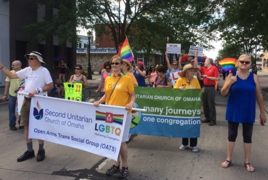 Church members holding banner as they march for LGBTQ justice in the Heartland Pride Parade