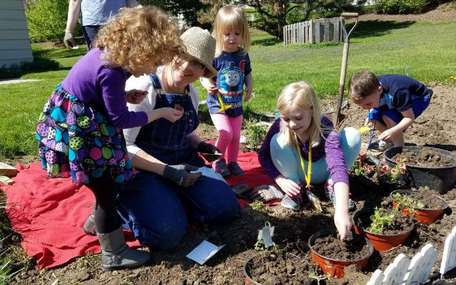 Children planting seeds in the Community Garden